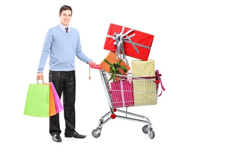 Full length portrait of a young male posing next to a shopping cart full of gifts isolated on white background Stock Photo - 16035145