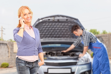 Smiling careless female talking on a mobile phone while in the background mechanic is checking her car photo