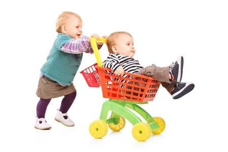 pushing: Peuter meisje duwt haar tweelingbroer in een stuk speelgoed wagen geïsoleerd op witte achtergrond