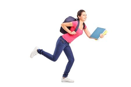 mochila: Joven estudiante mujer corriendo hacia adelante con el libro en la mano Foto de archivo