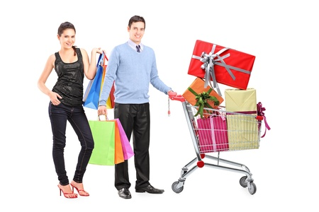 Couple holding bags and posing next to a shopping cart full of presents isolated on white  photo