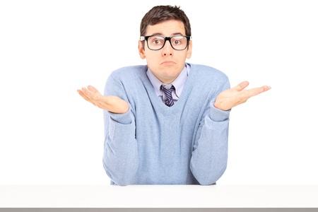preguntando: Dudoso joven sentado y haciendo gestos con las manos aisladas en fondo blanco Foto de archivo