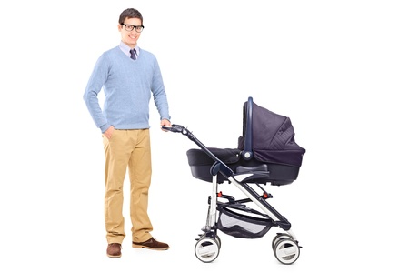 Full length portrait of a young father holding a baby stroller isolated on white background