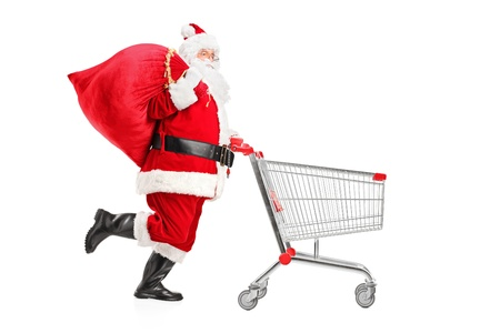 Santa Claus with a bag on his shoulder pushing an empty shopping cart isolated on white background photo