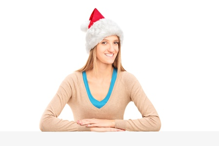Smiling female with santa claus hat sitting at a table isolated on white background photo