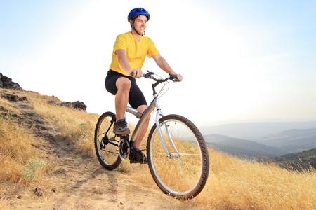 A view of a biker riding a mountain bike on a sunset