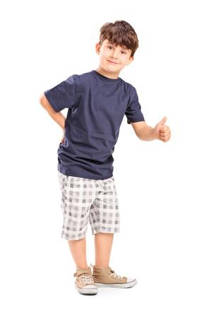 Ritratto di lunghezza completa di un giovane ragazzo dà un pollice in su, isolato su sfondo bianco