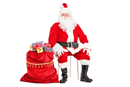 Santa Claus sitting with bag full of presents isolated on white background photo