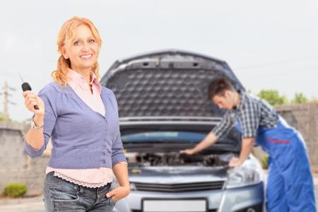 부주의 한: 배경 정비사에 그녀의 차를 확인하는 동안 키를 누른 상태에서 부주의 한 여성의 미소 스톡 사진