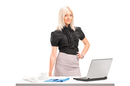 table skirt: Young professional woman standing next to office desk with laptop isolated on white background