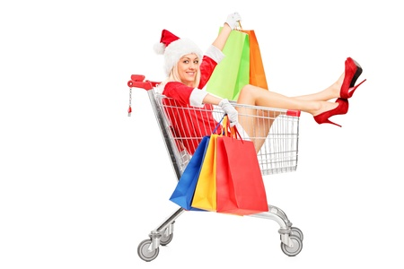 ���push cart���: A female in christmas costume holding shopping bags into a push cart isolated on white background