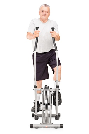 flywheel: Full length portrait of a mature man excersing on a cross trainer isolated on white background