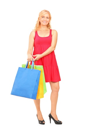 Full length portrait of a smiling mature woman holding shopping bags isolated on white background Stock Photo - 16118580