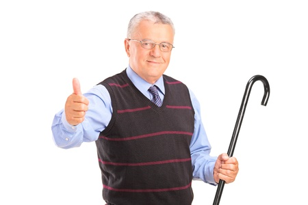 A senior man holding a cane and giving thumb up isolated on white background Stock Photo - 16118546