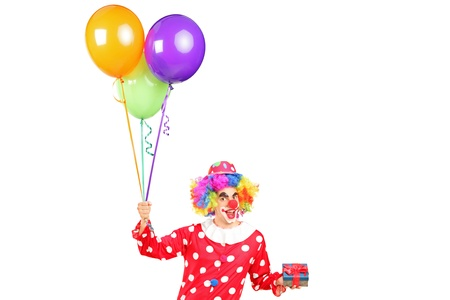 A male clown, happy joyful expression on face, with a bunch of balloons and a gift isolated on white background Stock Photo - 16243283