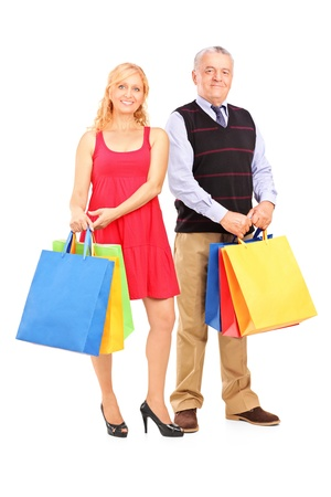 Full length portrait of a mature man and woman holding shopping bags isolated on white   Stock Photo - 16243239