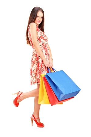 Full length portrait of a seductive female posing with shopping bags isolated on white background Stock Photo - 16243287