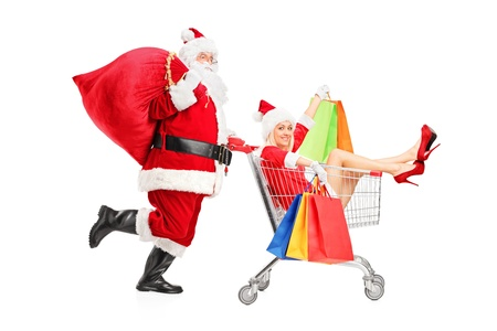 Santa Claus pushing a woman with shopping bag in a push cart isolated on white background photo