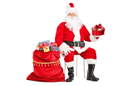 Santa Claus with a gift sitting next to a bag full of presents isolated on white background photo