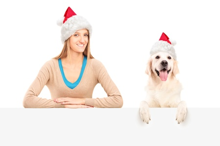 Smiling female and dog wearing santa claus hats and posing behind a blank panel photo
