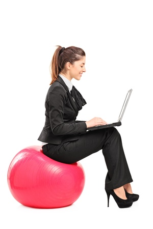 formal wear clothing: A busy woman sitting on a pilates ball and working on a notebook computer isolated against white background Stock Photo