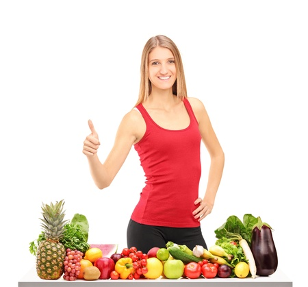 Female athlete giving thumb up behind a table full of healthy food isolated on white background Stock Photo - 16243246