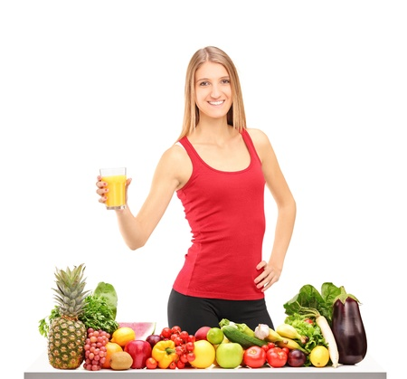 Female athlete refreshing with juice after exercise, behind a table full of healthy food isolated on white background Stock Photo - 16243247