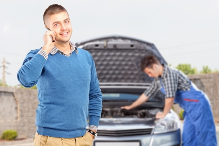 careless: Smiling careless guy talking on a cell phone while in the background mechanic is checking his car Stock Photo