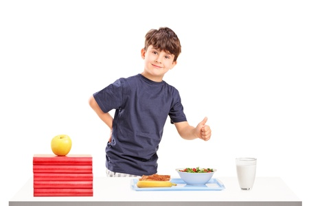 A happy boy giving a thumb up and table prepared for meal isolated on white background Stock Photo - 16243178