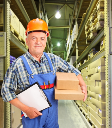 storeroom: A male worker in uniform holding boxes and clipboard at warehouse