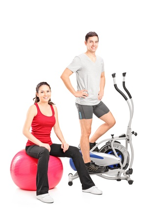 Athletic couple posing with a fitness equipment, cross trainer machine and pilates ball, isolated on white background photo