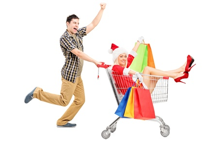 Excited person pushing a shopping cart and woman in christmas costume isolated on white background photo