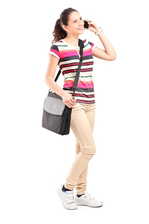 Full length portrait of a smiling school girl with shoulder bag talking on a phone isolated on white background