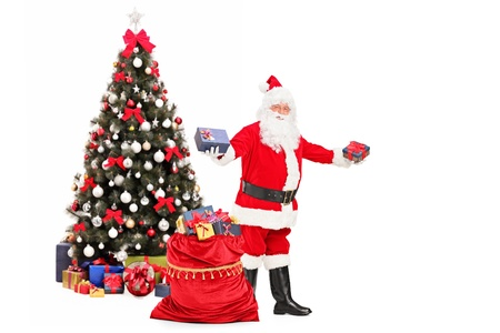 Santa Claus giving gifts from a bag full of presents and decorated christmas tree in the background photo