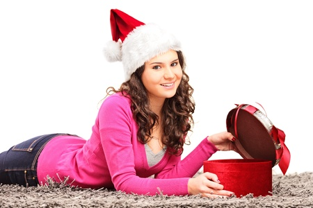 Smiling female with christmas hat lying down and opening a gift isolated on white background photo