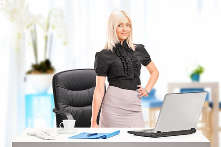 table skirt: Young businesswoman standing next to desk with laptop at her workplace