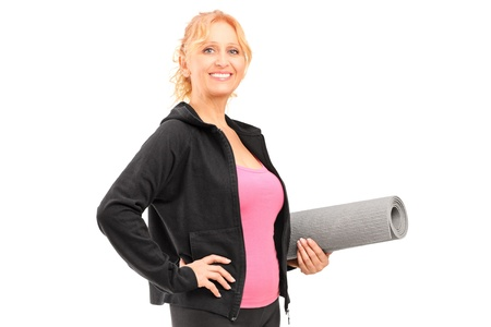 A mature female athlete holding a mat isolated on white background Stock Photo - 16320302