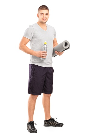 athletic wear: Full length portrait of a male holding a bottle of refreshment drink and a mat after an excerise isolated on white