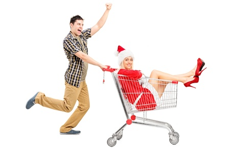 Guy pushing a woman wearing christmas costume in a shopping cart isolated on white background  photo