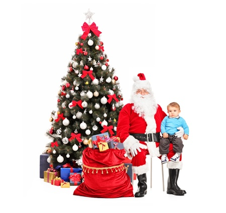 Santa Claus and child on his lap posing, a christmas tree in the background photo