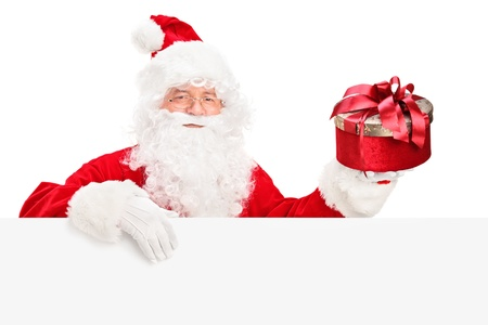 Santa Claus posing behind a blank billboard and holding a present isolated on white background photo