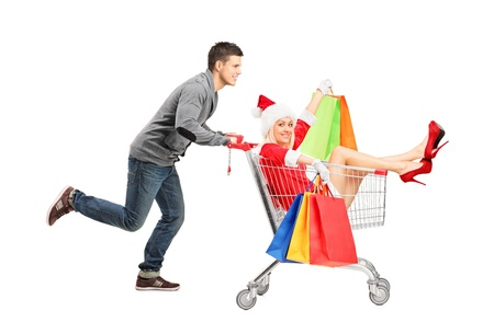 Happy guy pushing a female wearing christmas costume in a shopping cart isolated on white photo
