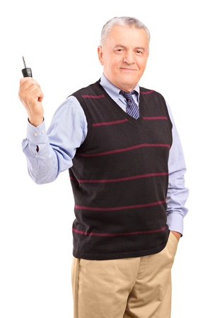 Smiling mature gentleman holding a car key isolated on white background Stock Photo - 16409017
