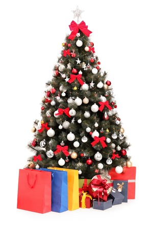 Studio shot of a decorated Christmas tree with gifts and bags isolated on white background photo