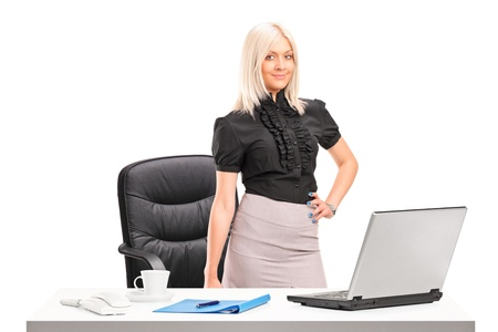 secretary skirt: Young businesswoman standing next to desk with laptop isolated on white background
