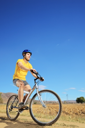 Young male in yellow shirt riding a bike on a sunny day, Macedonia Stock Photo - 16409006