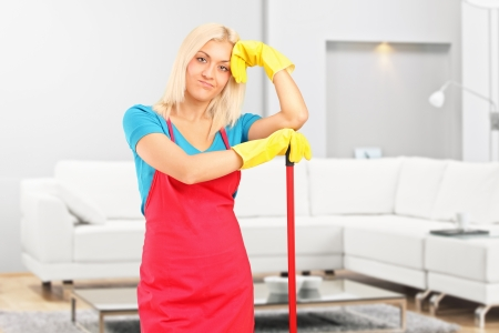 apartment cleaning: A tired female cleaner resting after cleaning an apartment Stock Photo