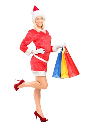 Full length portrait of a female in christmas costume holding shopping bags isolated on white background Stock Photo - 16501960