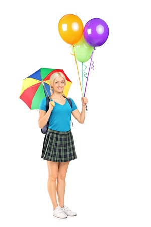 Full length portrait of a female student holding an umbrella and balloons isolated against white background Stock Photo - 16501958