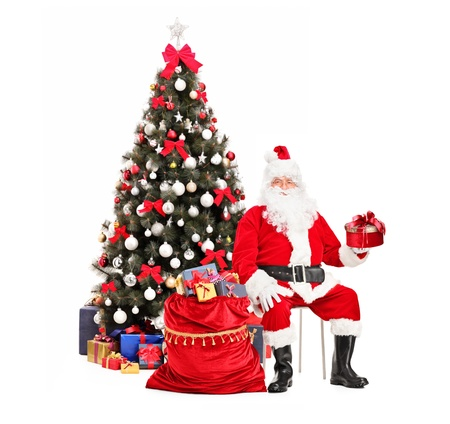 Santa Claus with a gift sitting next to a bag full of presents, christmas tree in the background photo